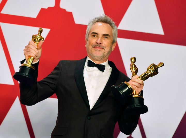 """Roma"" director Alfonso Cuarón holding the film's three Oscars."
