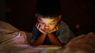 Little asian kid alone watching tablet device, lying on white duvet bed with chin on hands, in background darkness bedroom night time. Colourful bright light from screen reflex on the boy face.