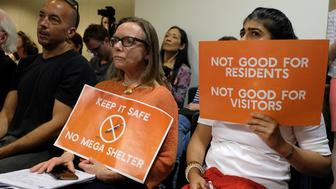 A pair of women opposed to a proposed homeless shelter hold up signs during a meeting of the Port Commission Tuesday, April 23, 2019, in San Francisco. San Francisco port commissioners are deciding whether to approve a new homeless shelter along the city's touristy and residential Embarcadero. (AP Photo/Eric Risberg)