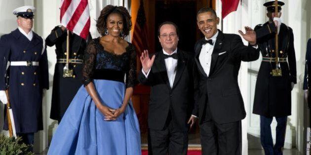 François Hollande a tavola tra Barack Obama e Michelle. Abito firmato Carolina Herrera per la first lady...