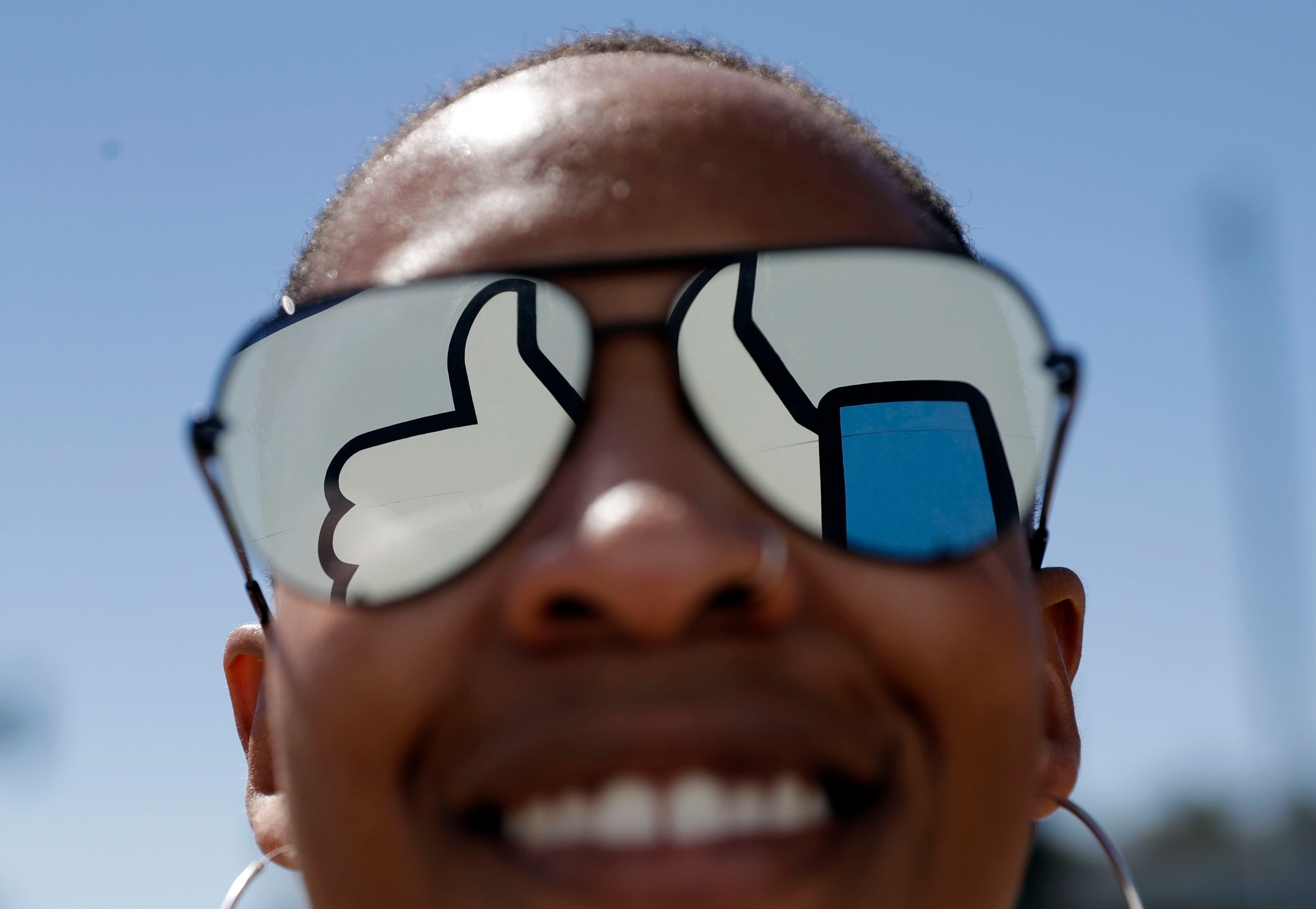In this March 28, 2018, file photo, a visitor poses for a photo with the Facebook logo reflected on her sunglasses at the company's headquarters in Menlo Park, Calif. Facebook revealed Wednesday, April 4, that tens of millions more people might have been exposed in the Cambridge Analytica privacy scandal than previously thought and said it will restrict the user data that outsiders can access. (AP Photo/Marcio Jose Sanchez)