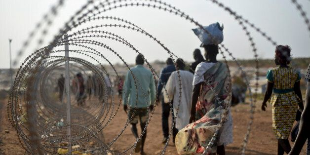 FILE- In this file photo taken Tuesday, Jan. 19, 2016,displaced people walk next to a razor wire fence at the United Nations