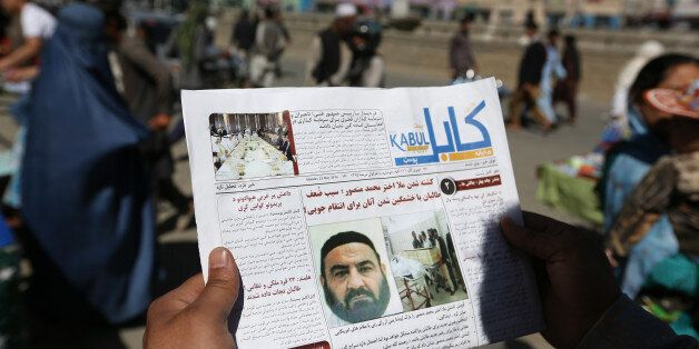 An Afghan man reads a local newspaper with photos the former leader of the Afghan Taliban, Mullah Akhtar Mansoor, who was kil