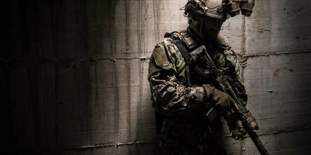 A combat ready special operation forces soldier with a MP7 silenced submachine gun and a night vision google.