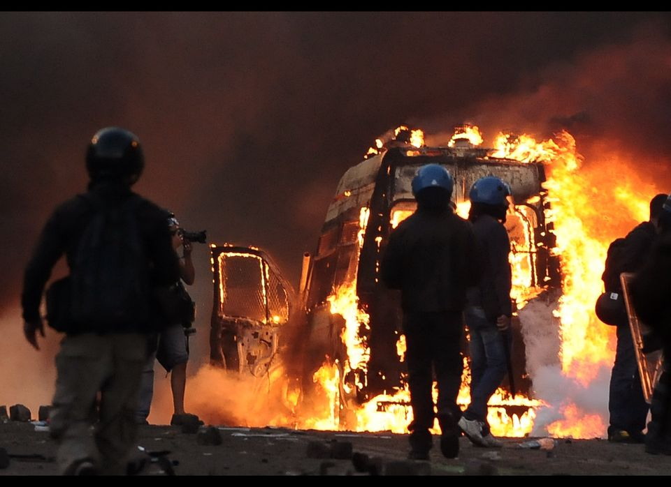Anti-riot policemen walk by a Police van in fire during a demonstration in Rome on October 15, 2011. Tens of thousands marche