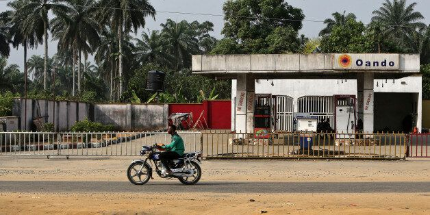 A man rides a motorcycle past a closed Oando Plc gas station in Port Harcourt, Nigeria, on Thursday, Jan. 14, 2016. With his