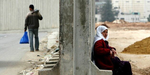 A Palestinian woman sits on part of the Israeli security barrier in the West Bank town of Ram near the checkpoint Qalandia Fe