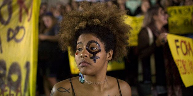 A woman wearing a female gender symbol attends a protest against the gang rape of a 16-year-old girl in Rio de Janeiro, Brazi