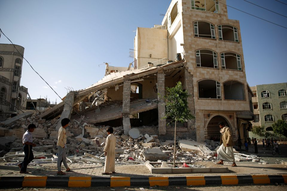 People walk past a house destroyed by a Saudi-led airstrike in Sanaa, Yemen, Tuesday, Sept. 8, 2015. (AP Photo/Hani Mohammed)