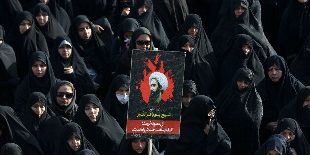 FILE -- In this Monday, Jan. 4, 2016 file photo, an Iranian woman holds up a poster showing Sheikh Nimr al-Nimr, a prominent