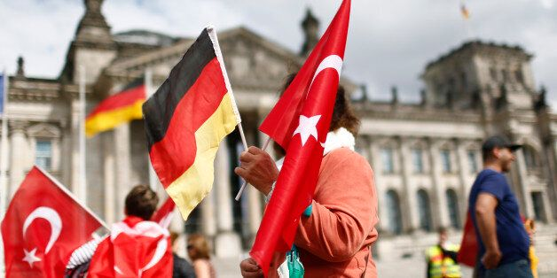 Demonstrators hold Turkish and German flags in front of the Reichstag, the seat of the lower house of parliament Bundestag in