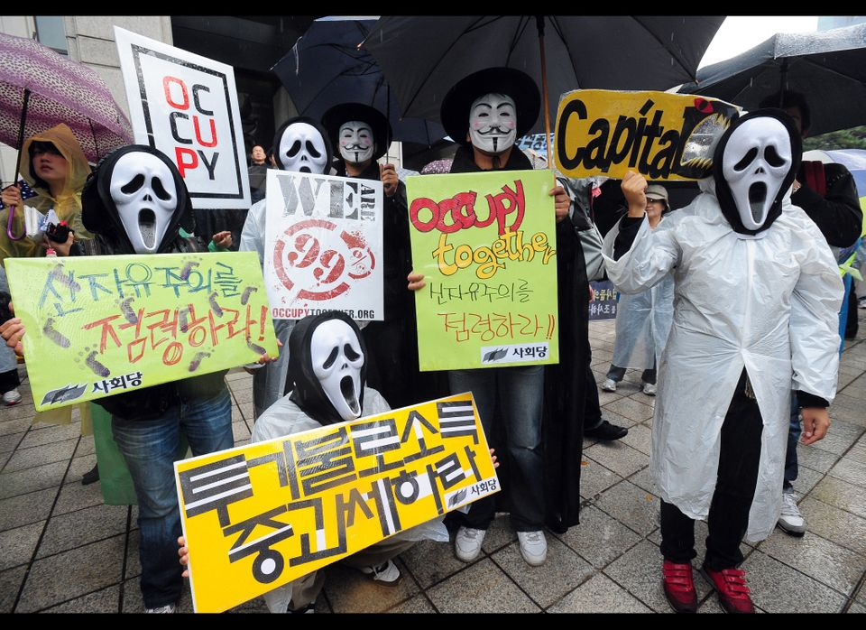 South Korean protesters wearing masks hold up banners during the 'Occupy Seoul' rally as part of the worldwide protest inspir
