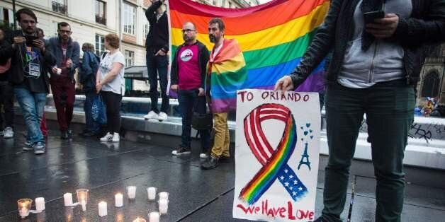 People and members of the gay community gather for a vigil near the Beaubourg art center in downtown Paris on June 12, 2016,