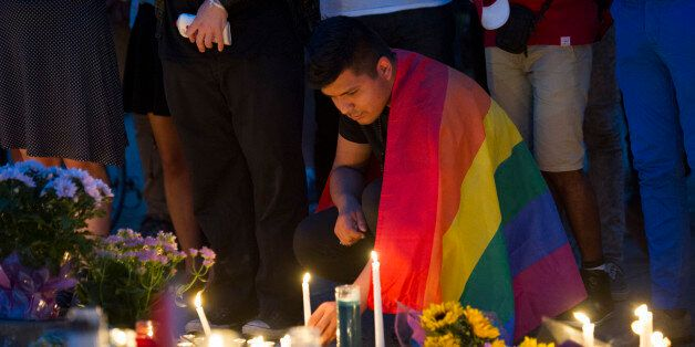 An unidentified man, wrapped in a Rainbow Flag, lights a candle during a vigil in Washington, Monday June 13, 2016, hosted by