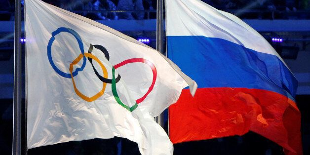 The Russian national flag (R) and the Olympic flag are seen during the closing ceremony for the 2014 Sochi Winter Olympics, R