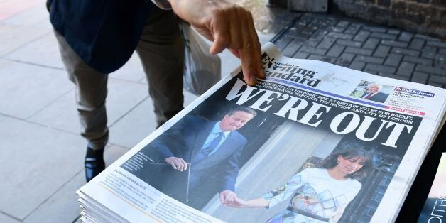 A man takes a copy of the London Evening Standard with the front page reporting the resignation of British Prime Minister Dav