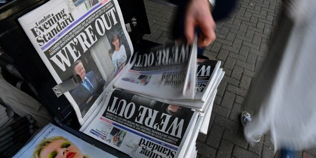 A man takes a copy of the London Evening Standard newspaper with the front page reporting the resignation of British Prime Mi