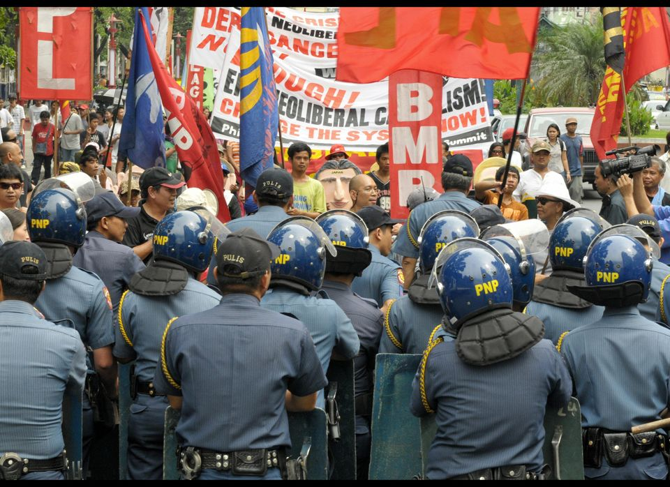 Riot police block protesters as they stage a rally and march toward the U.S. embassy in the Manila on November 15, 2008, to c