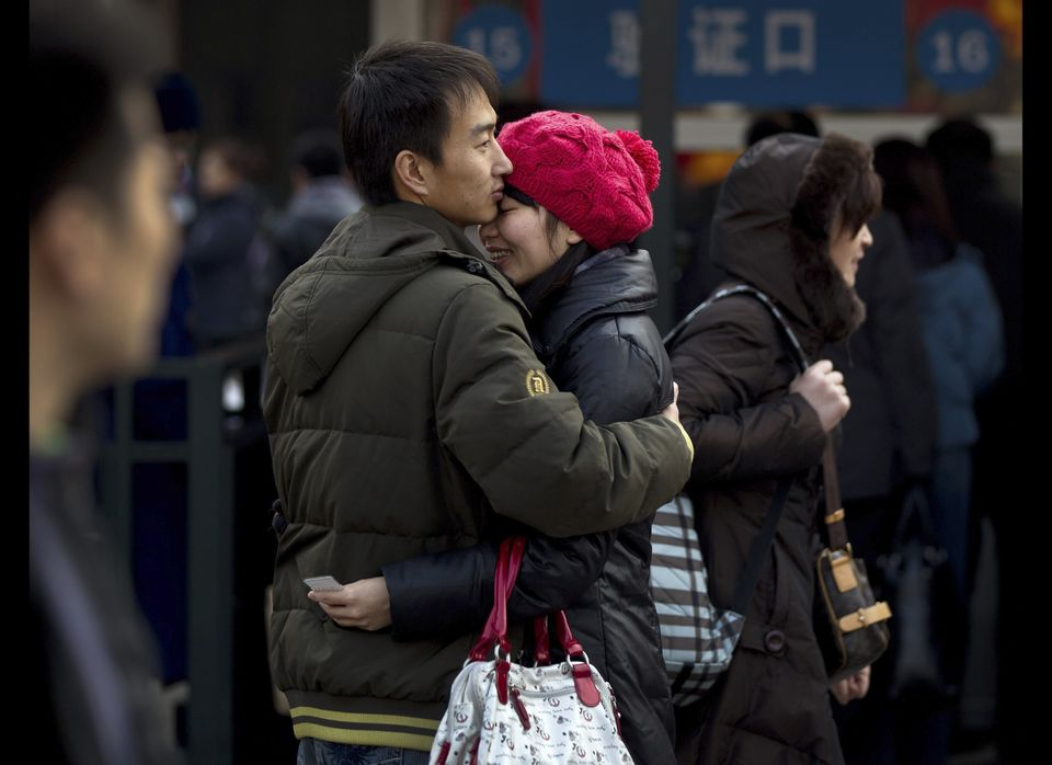 A Chinese couple hug as they bid farewell outside Beijing train station in Beijing, China, Sunday, Jan. 8, 2012. Millions of