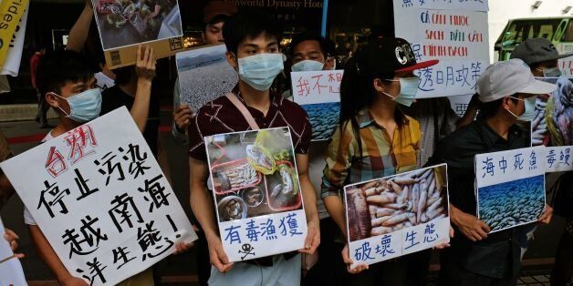 Vietnamese living in Taiwan display placards and images of dead fish, claimed by protesters to be caused by Taiwan's Formosa