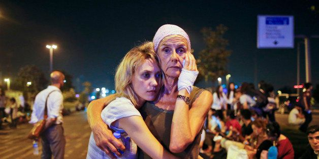 Passengers embrace each other as they wait outside Istanbul's Ataturk airport, early Wednesday, June 29, 2016 following their