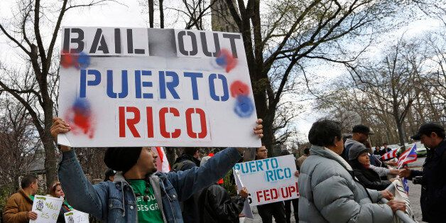 A demonstrator protests the Federal Reserve's failure to bail out Puerto Rico outside International House, Thursday, April 7,