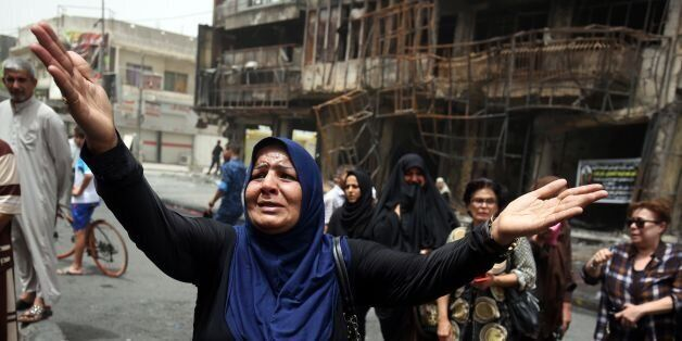 An Iraqi woman reacts on July 4, 2016 at the site of a suicide-bombing attack which took place a day earlier in Baghdad's Kar