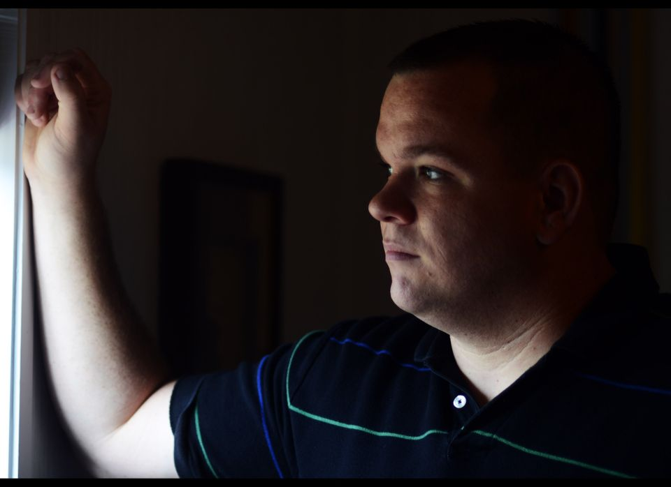 Wounded Marine Corp veteran Adam Lewis looks out the window at his home on Monday, Nov. 7, 2011 in Yulee, Fla. Lewis was shot