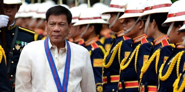 Philippine President Rodrigo Duterte walks past honour guards before Philippine National Police (PNP) chief Ronald Bato Dela