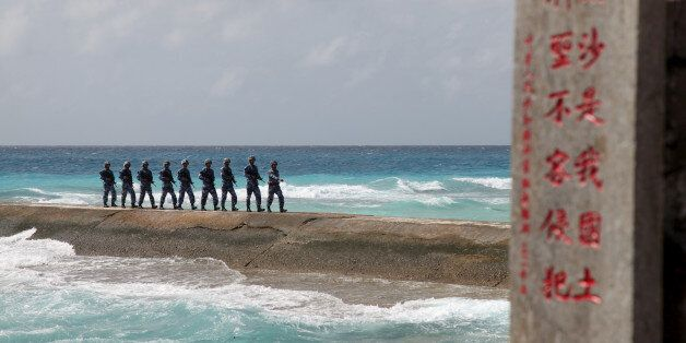 Soldiers of China's People's Liberation Army (PLA) Navy patrol near a sign in the Spratly Islands, known...