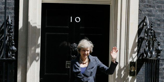 Britain's Home Secretary Theresa May waves to the media as she leaves after attending a cabinet meeting...