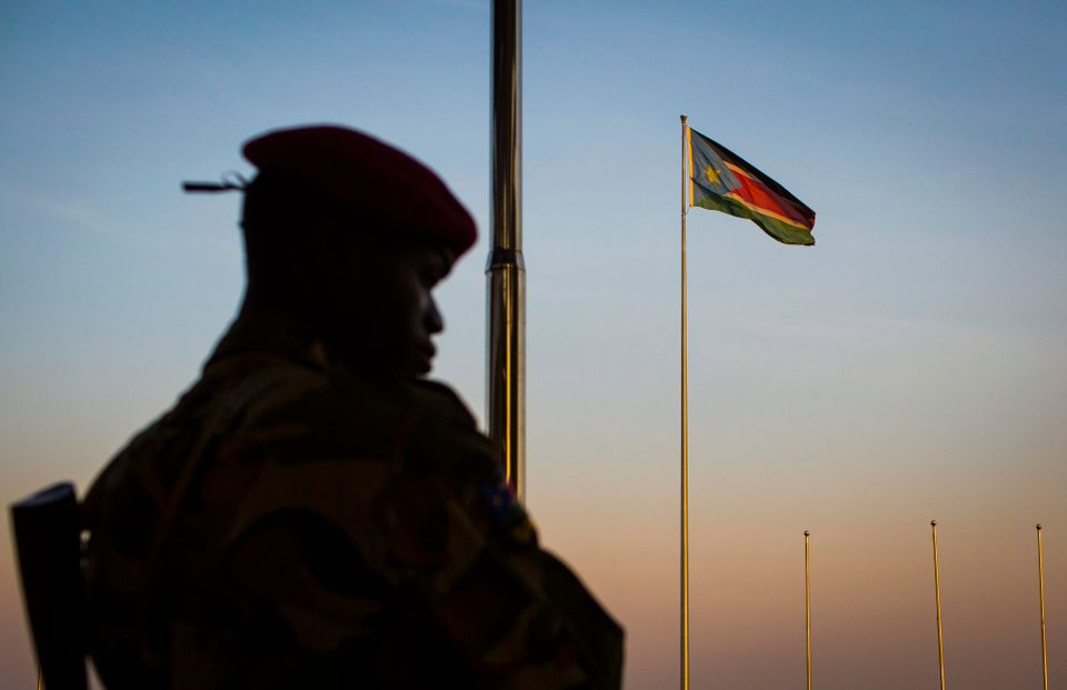 A South-Sudanese government soldier stands guard as a South Sudanese flag flies in the background, at the memorial to politic