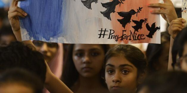 Indian students take part in a prayer meeting in memory of the victims of a truck attack in the French city of Nice at the Ma