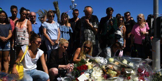 NICE, FRANCE - JULY 15:  People visit the scene and lay tributes to the victims of a terror attack on the Promenade des Angla