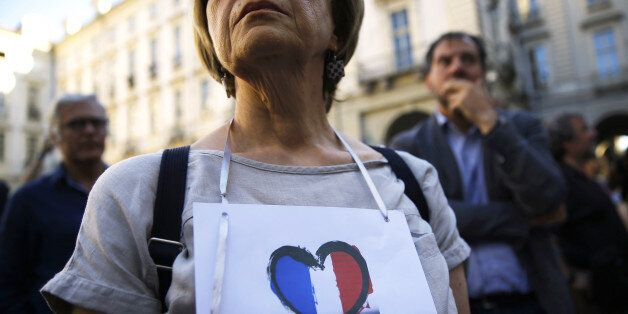 A woman wears a banner displaying the colours of France's flag in a heart during a minute of silence in front of the City Hal