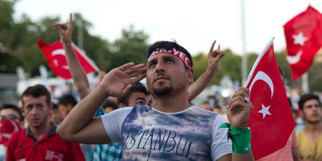 A protester salutes as he takes part in a rally in Taksim Square, Istanbul, Sunday, July 17, 2016. The Turkish government acc