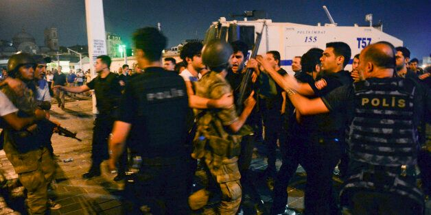 Turkish soldiers, arrested by civilians, are handed to police officers in Taksim Square in Istanbul, Turkey, early Saturday,