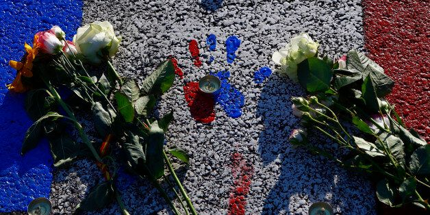 A painting with the colors of the French flag covers the asphalt near a makeshift memorial to honor the victims, three days a