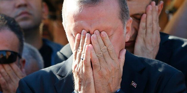 Turkish President Recep Tayyip Erdogan prays during a funeral service for a victim of the thwarted coup in Istanbul, Turkey,