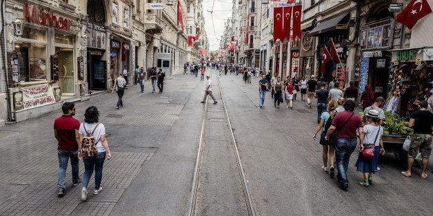 Visitors walk past retail stores along a half empty Taksim street in Istanbul, Turkey, on Monday, July 18, 2016. Tourism is an essential source of foreign currency to finance Turkey's current-account deficit and employs 8 percent of the nation's workforce. Photographer: Ismail Ferdous/Bloomberg via Getty Images