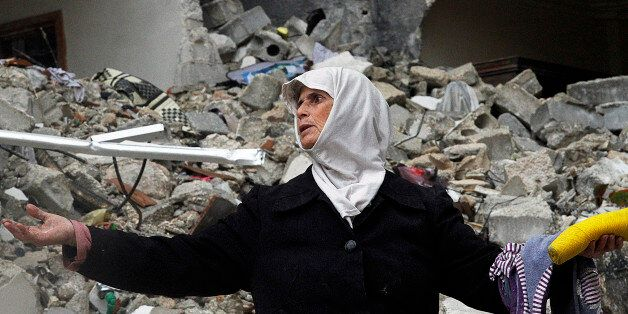 FILE - In this Wednesday, Feb. 6, 2013 file photo, a Syrian woman stands amid the ruins of her house which was destroyed in a