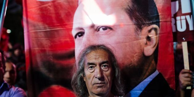 A man stands in front of a picture of Turkish President Recep Tayyip Erdogan during a rally at Kizilay Square in Ankara on Ju