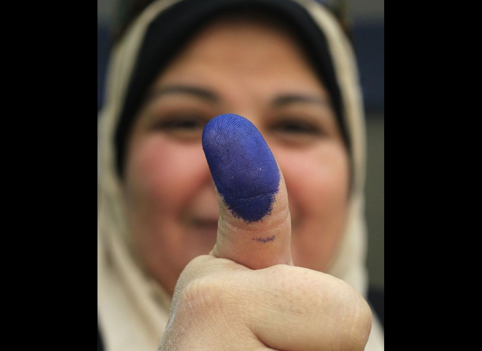 An Egyptian woman shows her ink-stained thumb after voting at a polling station in the Manial neighbourhood of Cairo on Novem
