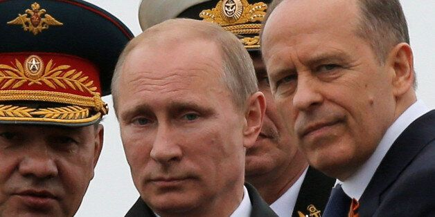 Russian President Vladimir Putin (C), Defence Minister Sergei Shoigu (L) and Russia's Federal Security Service (FSB) Director
