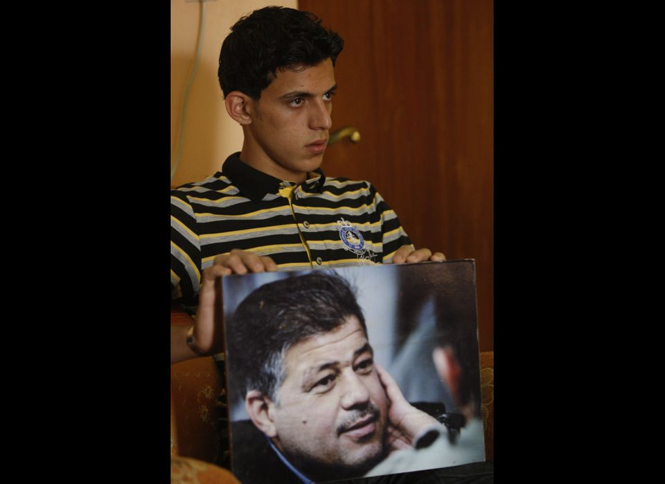 <em>Samer, son of slain Reuters news agency chauffeur Saeed Chmagh, shows a picture of his father during an interview at his