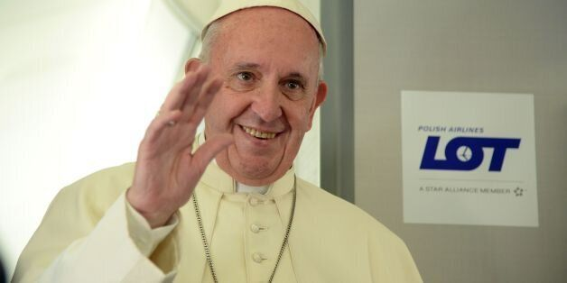Pope Francis waves during a press conference on the plane after his visit to Krakow for the World Youth Days, on July 31, 201