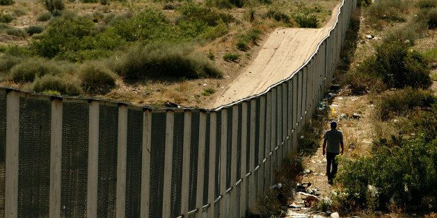 CIUDAD JUAREZ, CHIHUAHUA - JUNE 29:  A man walks along the border fence between the U.S. and Mexico on June 29, 2007 in the A