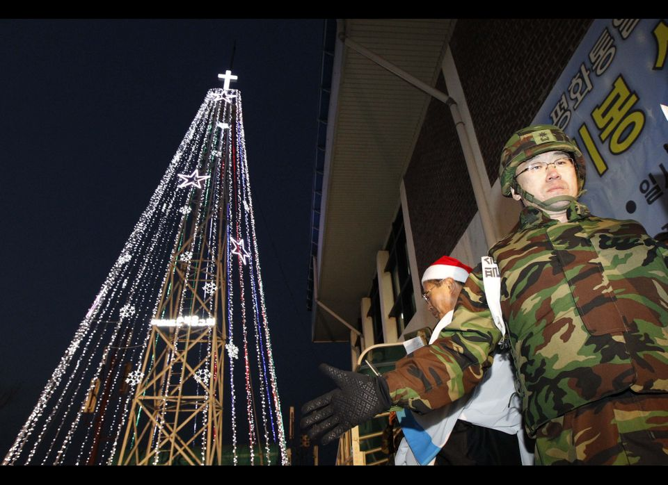 A South Korean military officer stands guard as Christians prepare a lighting ceremony in front of a Christmas tree atop a mi