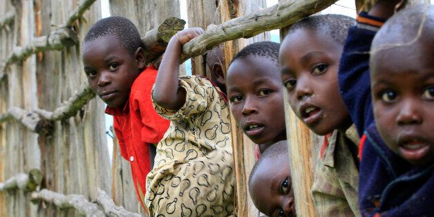 Congolese refugee children play on wooden fencing erected to secure the Nyakabande refugees transit camp in Kisoro district, 491 km (305 miles) west of Ugandan capital Kampala November 9, 2013. REUTERS/James Akena (UGANDA - Tags: SOCIETY IMMIGRATION POVERTY TPX IMAGES OF THE DAY CIVIL UNREST)