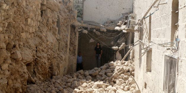 Residents inspect their damaged homes after an airstrike on the rebel-held Old Aleppo, Syria August 15, 2016. REUTERS/Abdalrh